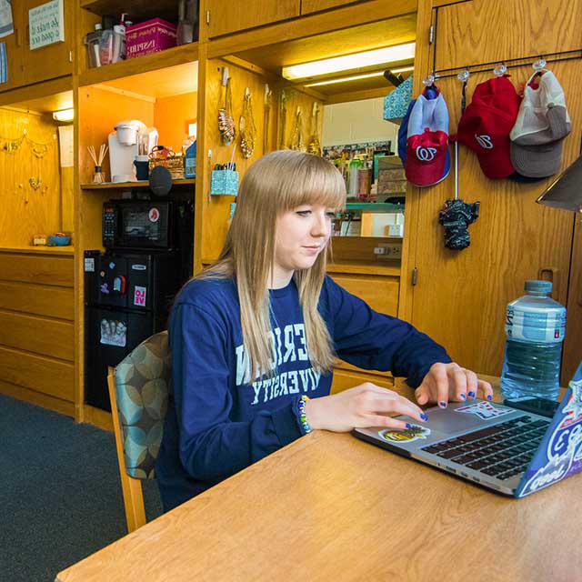 A first-year student at her desk in her room 在 Anderson Hall.